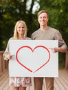 Romantic couple with white board and heart on it summer holidays love travel relationship advertisement concept bridge pointing Stock Images