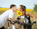 Romantic couple young beautiful with flower on sporty bicycles on sunflowers field background Royalty Free Stock Image