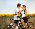 Romantic couple young beautiful on sporty bicycles against sunflowers field background Stock Photography