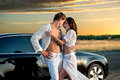 Romantic couple young standing before car against sunset Royalty Free Stock Image