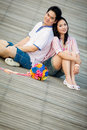 Romantic couples sitting over wooden pier Royalty Free Stock Photo