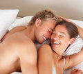 Romantic and cute young couple laughing in bed Royalty Free Stock Photo
