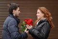 Romantic date young man presenting a bunch of red roses to his men cute girlfriend Royalty Free Stock Photos