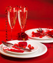 Romantic dinner image of white festive plate served with silver cutlery and wineglasses and decorated with heart shaped candle and Stock Photography