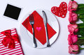 Romantic dinner: plate, cutlery and roses on a white background. Royalty Free Stock Photo