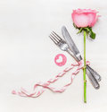 Romantic dinner table place setting with fork knife pink rose and heart on white wooden background top view love symbol valentine Stock Photo