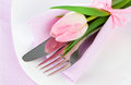 Romantic dinner table setting with roses tulips and cutlery on a white background copy space Stock Image