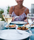 Romantic dinner with white wine in the background a girl is out of focus Royalty Free Stock Image