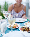 Romantic dinner with white wine in the background a girl is out of focus Royalty Free Stock Photos