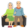 Romantic elderly couple sitting close together on a sofa white background Royalty Free Stock Photography