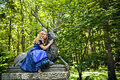 Romantic girl in the fairytale forest wearing dirndl and sitting on deer Stock Image