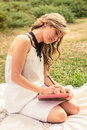 Romantic girl writing in a diary sitting outdoors portrait of young woman over the grass relax outdoor time concept Royalty Free Stock Image
