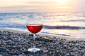 Romantic glass of wine sitting on the beach at colorful sunset glass of red wine against sunset red wine on the sea ocean beach Royalty Free Stock Photography