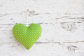 Romantic green dotted heart shape hanging above white wooden sur surface on a nail shabby chic background for a greeting Royalty Free Stock Image