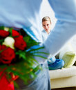 Romantic guy hiding flowers behind his back Royalty Free Stock Photography