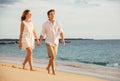 Romantic happy couple walking on beach at sunset