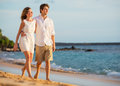 Romantic happy couple walking on beach at sunset smiling with arms around each other man and women in love Royalty Free Stock Photos