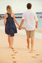 Romantic happy couple walking on beach at sunset smiling holding hands man and women in love Stock Photos
