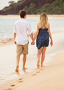 Romantic happy couple walking on beach at sunset smiling holding hands man and women in love Stock Photography