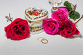 Romantic heart shaped artistic jewelry box with bright red and pink roses with gold engagement rings on light background. Royalty Free Stock Photo