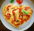 Romantic heart shaped italian pizza overhead view of a topped with a vegetarian topping of golden melted cheese and tomato on a Royalty Free Stock Image