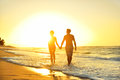 Romantic honeymoon couple in love at beach sunset holding hands walking on beautiful waterfront lovers or newlywed married Royalty Free Stock Images