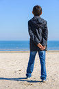 Romantic kid on beach boy looking at sea fall clothes bluejeans autumn or summer late back view hand in hand Stock Images