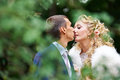 Romantic kiss bride and groom through the foliage on wedding walk Stock Photos