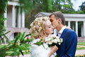 Romantic kiss bride and groom on wedding walk in park Stock Photos