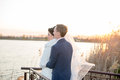Romantic landscape, the newlywed couple posing at sunset near the river, the bridegroom holds the hand of a bride Royalty Free Stock Photo