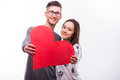 Romantic love hipster couple  with a red heart in hands look at camera. Royalty Free Stock Photo