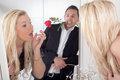 Romantic man and a beautiful woman reflection in the mirror of nonchalant men with red rose between his teeth watching blond women Royalty Free Stock Photos