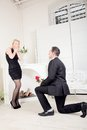 Romantic man proposing to his girlfriend shocked kneeling down on the floor in front of her with a rose and the ring box in Royalty Free Stock Photo