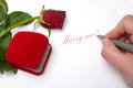 Romantic marriage proposal with a rose and a jewellery box Stock Photos