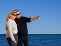 Romantic mature couple pointing to copyspace at the coast Royalty Free Stock Photo