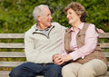 Romantic mature couple sitting on bench - Outdoor Stock Image