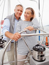 Romantic mature couple steering the boat Stock Image