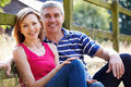 Romantic middle aged couple relaxing on walk in countryside smiling to camera Royalty Free Stock Photos