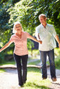 Romantic middle aged couple walking along countryside path holding hands smiling Royalty Free Stock Photography