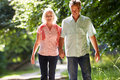 Romantic middle aged couple walking along countryside path holding hands in the summer Stock Image