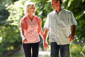 Romantic middle aged couple walking along countryside path looking at each other whilst holding hands Stock Photography