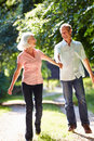 Romantic middle aged couple walking along countryside path whilst looking at each other smiling Stock Image