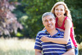 Romantic middle aged couple walking in countryside smiling to camera Royalty Free Stock Image
