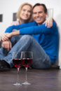 Romantic moments beautiful middle aged couple sitting on the floor and holding hands while two glasses of red wine standing on the Stock Photo