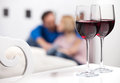 Romantic moments beautiful middle aged couple sitting on the floor and holding hands while two glasses of red wine standing on the Stock Photos