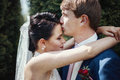 Romantic newlywed couple kissing and hugging in park closeup Stock Images