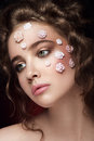 Romantic nude young beautiful girl with white flowers on her face and soft curls on dark background.