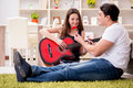 The romantic pair playing guitar on floor