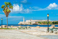 Romantic park in havana with a view of the castle of el morro and lighthouse at bay entrance Royalty Free Stock Image