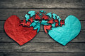 Romantic relationship concept two hearts exchange feelings as made of torn crumpled paper on weathered wood as symbol for romance Royalty Free Stock Images